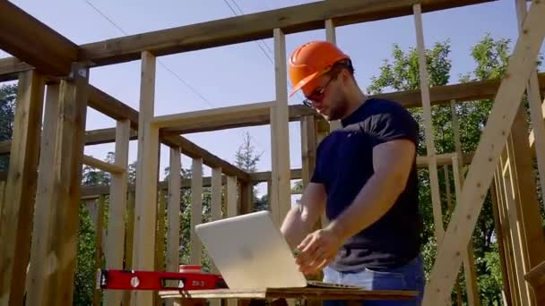 építő keres a képernyőn a laptop-ra egy szerkezet telek, ház, épület szint és támogatja ellenőrzése