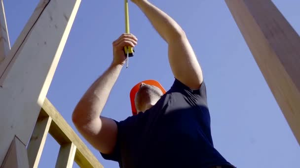 tilt up view of working builder in a building site against blue sky, measuring length