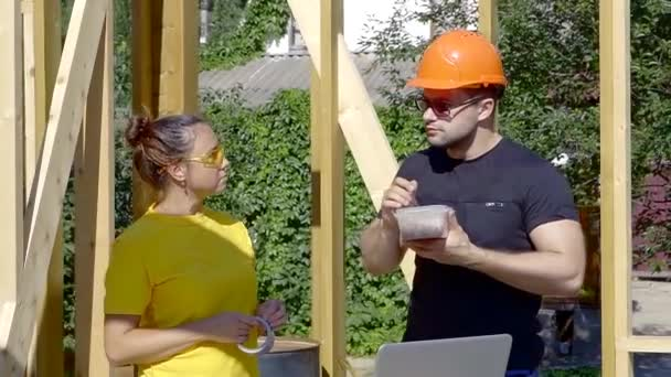 builder man is snacking during dining break in a construction area in summer day, brunette woman is standing near