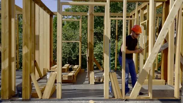 felnőtt ember, hogy méréseket, fából készült gerendák keret új házat építés alatt, szalag és a szint