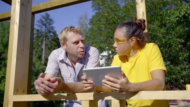 middle aged man is explaining to brunette woman, holding tablet, standing on a construction area in villa