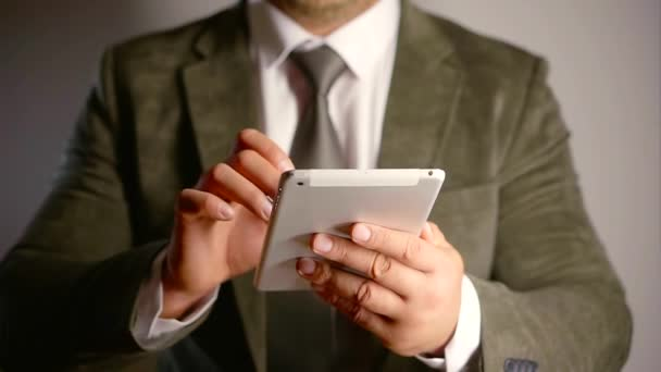 Businessman using white tablet wearing luxury suit in a studio with grey background.