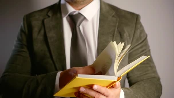 Close up shot of a man in a suit and tie holding a book, grey background of a studio.