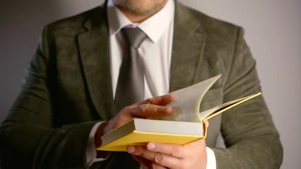 adult man is wearing suit is reading book, turning sheets, correcting his tie, close-up