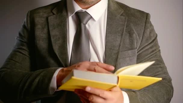 vážná věc člověk čte knihu, obracející stránky, stojící na šedou stěnu pozadí