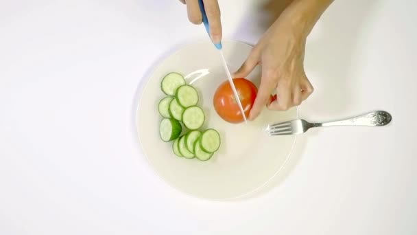 woman is cutting red tomato on white plate with cut cucumbers, preparing a vegetable salad
