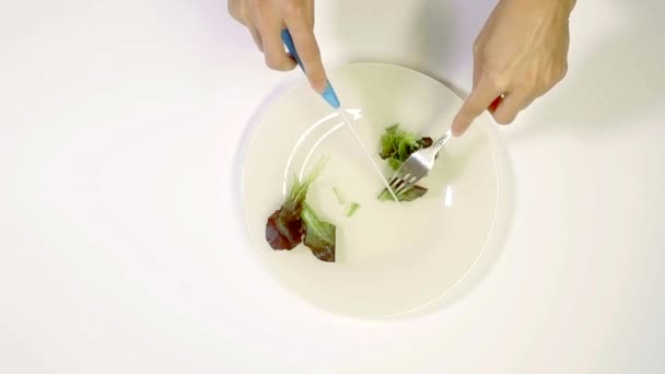 chef is slicing lettuce on white dish, using metal tableware, close-up of hands from top