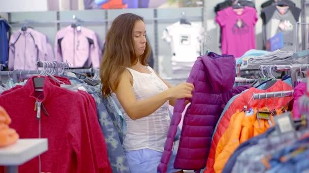 51cd5bcd5 Mulher bonita morena está observando um casaco quente numa área comercial  de loja de roupas de esporte– gráficos de vetor