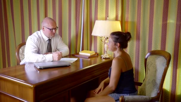 woman in the office of a lawyer for a consultation. a man in a shirt tie and glasses explains everything and demonstrates on paper