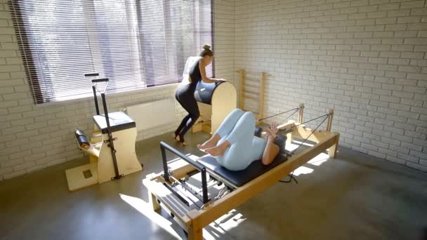 Pilates teacher corrects the position of the clients body on the simulator. therapeutic physical culture
