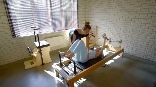 Pilates teacher corrects the position of the clients body on the simulator. physical education of the body