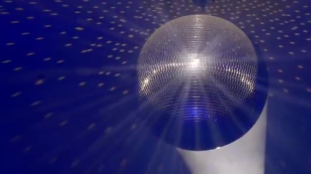 Disco zrcadlová koule odráží modré a červené světlo, paprsky světla po stranách
