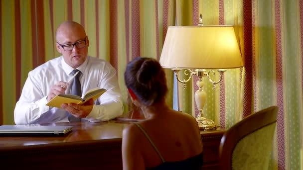 obchodní muž v bílé košili a kravatu v kanceláři sedí u stolu s kolegou o práci a kontroluje informace v knize