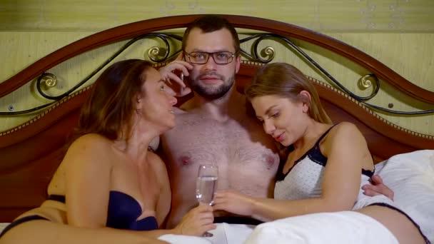 zwei süße Mädchen liegen mit einem ihrer Männer im Bett und umarmen ihn