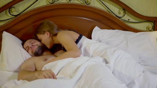 Portrétní snímek mladé ženy probuzení brzy ráno v posteli s pestré noční a pak probuzení svého manžela