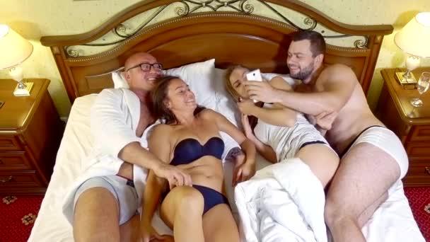 zwei Paare im selben Bett sind mit Mobiltelefonen ausgestattet. Pyjama-Party