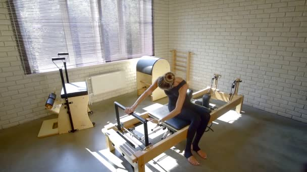 slender girl in a black sports jumpsuit performs stretching exercises in the Pilates simulator