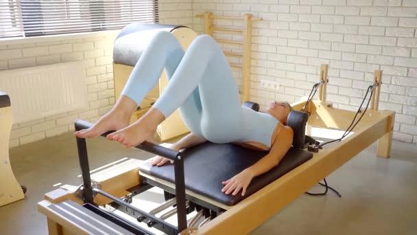 terapeutické cvičení na simulátoru Pilates. dívka, po zranění se pokusí provést cvičení k posílení zad
