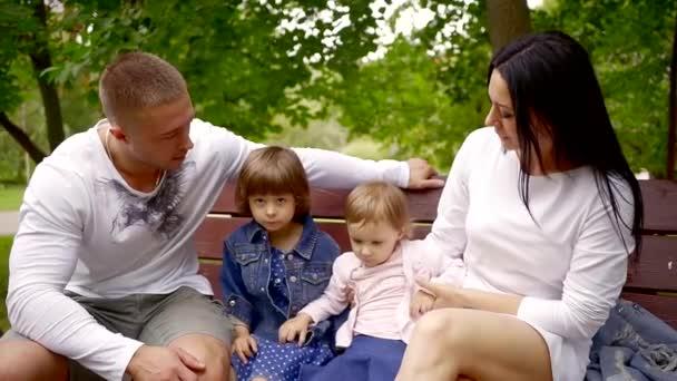 šťastná rodina s dvě malé dcery jsou procházky v parku v létě, otec a matka sedí na lavičce