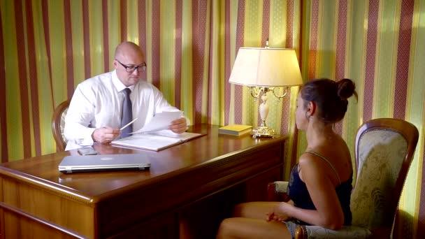 Dospělý samec bankovní zaměstnanec radí brunetka žena v soukromé kanceláři, že on je čtení dokumentů