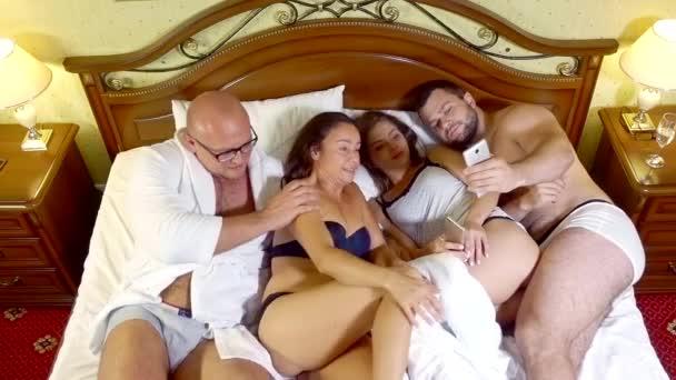 zwei Frauen und zwei Männer liegen im Bett und fotografieren ihre Firma mit der Kamera des Mobiltelefons