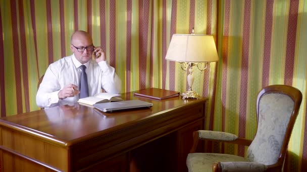 businessman is conducting telephone conversations in his office, looking in his diary