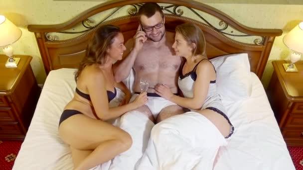 schöner muskulöser Kerl mit Brille telefoniert, während zwei Mädchen in Unterwäsche ihn im Bett umarmen.