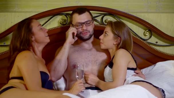 erfolgreicher Mann telefoniert und umarmt zwei Mädchen im Bett.