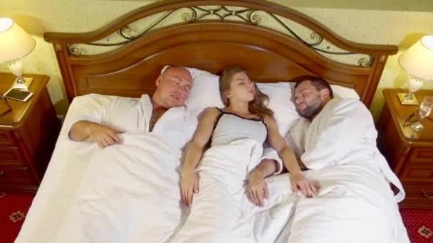 Frau wacht morgens mit großen Jungs im Bett auf.