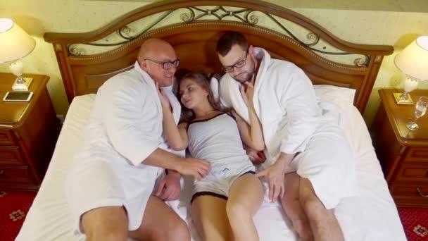Zwei Jungs mit Spaß mit Mädchen im Bett eines Hotelzimmers.