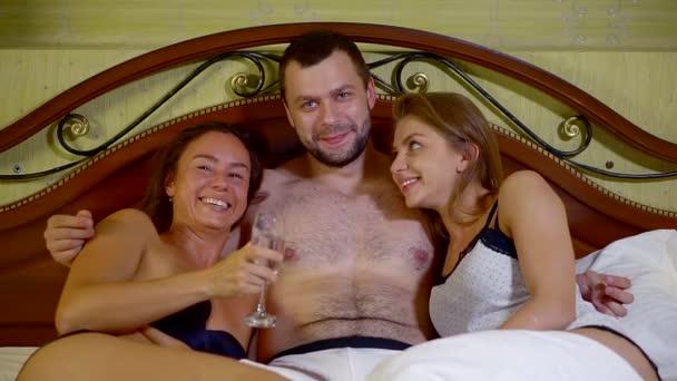 Porträt eines jungen gutaussehenden heißen Mannes mit Brille, der mit sexy Mädchen im Bett liegt. Selbstbewusster Kerl verbringt Nacht mit zwei Frauen im Hotel.