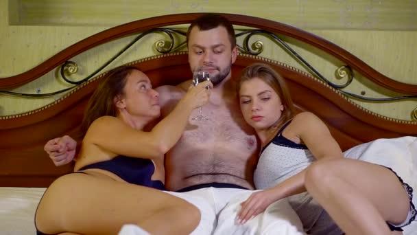 sinnliche dunkelhaarige Mann umarmt und streichelt Körper von zwei schönen Frauen, blond und brünett, im Bett liegend