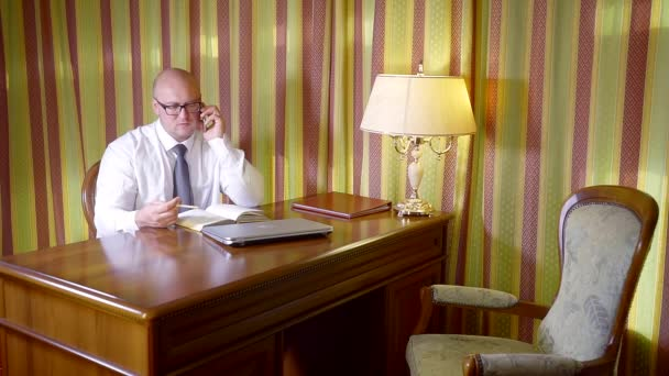 businessman is conducting telephone conversations in his office, looking in his diary, sitting alone at table