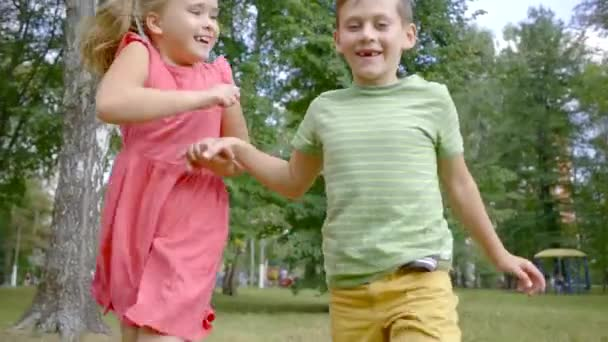 two preschoolers kids are running in a park in summer day, girl and boy are holding hands