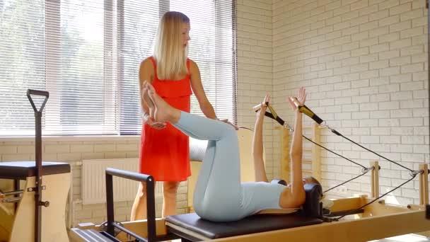 ženské trenér vysvětluje klienta žena fitcentru jak provádění pilates cvičení na stůl