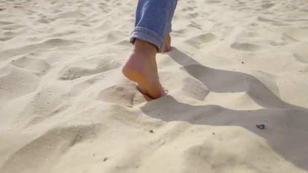Zadní pohled na ženy nohy naboso v džínách chůzi na písečné pláži. odpočinek u moře na zlatého písku. Úhel kamery nízká a slowmotion.
