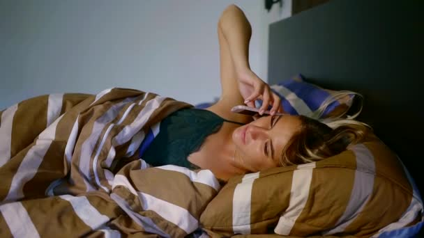 Beautiful girl lying on the side of a bed under blanket and talking on the phone.