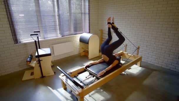 Sportovní žena dělá strečink a core cvičení na pohyblivé plošině, pilates