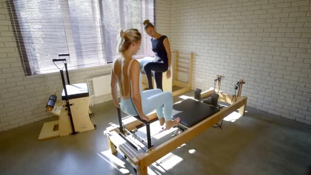 Fitness instructor explaining leg exercise on a reformer to client.