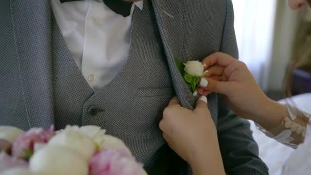 Zár megjelöl szemcsésedik-ból egy nő rögzítés boutonniere esküvői ceremónia előtt a vőlegény öltöny zseb