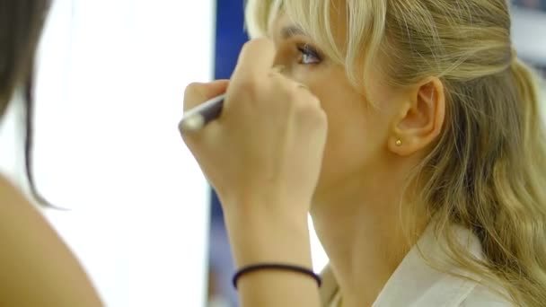 Professional makeup artist is applying foundation on face of client woman  before filming