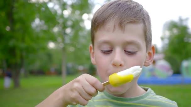Detailní záběr dospívající chlapce lízání zmrzliny v parku