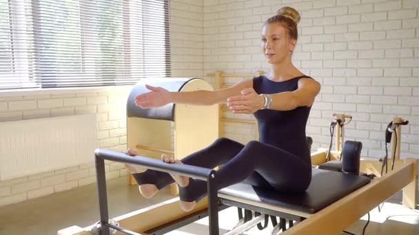 Sportovní žena táhnoucí se její horní část těla pomocí reformátor v pilates třídy