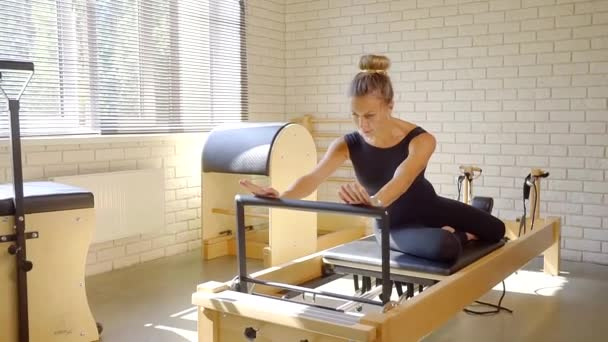 Úžasné sportovní žena pomocí reformátor v pilates třídy.