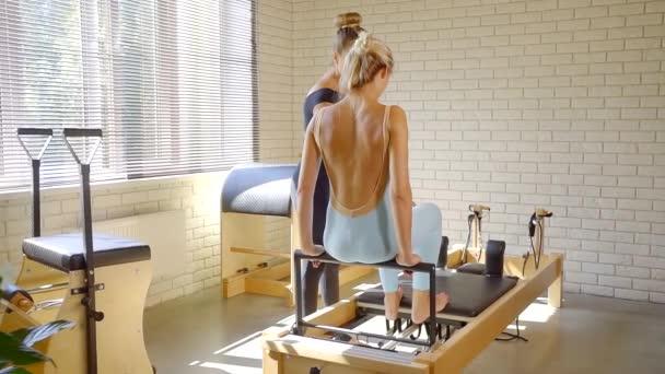 Okouzlující žena fitness cvičením nohou na reformátora zařízení.