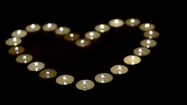 Big heart made of lit candles in dark room.