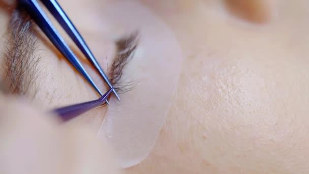 Close-up shot řasy prodloužení procedury v salonu krásy, profesionální kosmetička práci