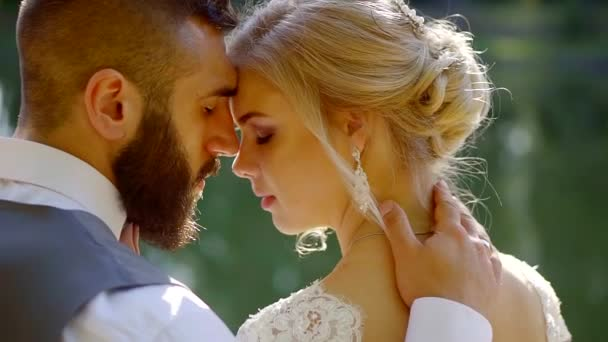 romantic loving groom and bride are hugging, touching by foreheads in sunny day, close-up