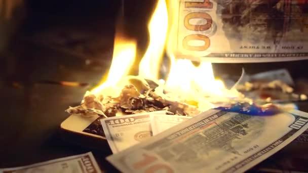 člověk je házet bankovky sto dolarů v ohni, smartphone a další papírové peníze