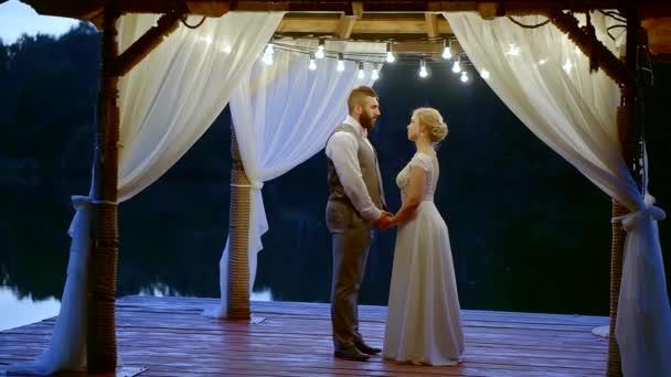 Ženich a nevěsta je líbání a drželi se za ruce, stojící dřevěné verandě večer